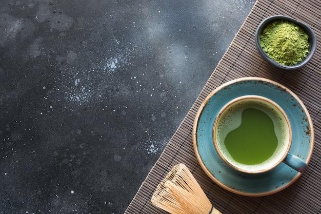 黒いテーブルの上の有機グリーン抹茶。 Premium写真