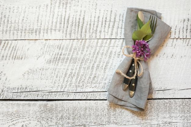 白い木製のテーブルにカトラリーとライラックの花で春のお祝いテーブルの設定。スペースをコピーします。 Premium写真