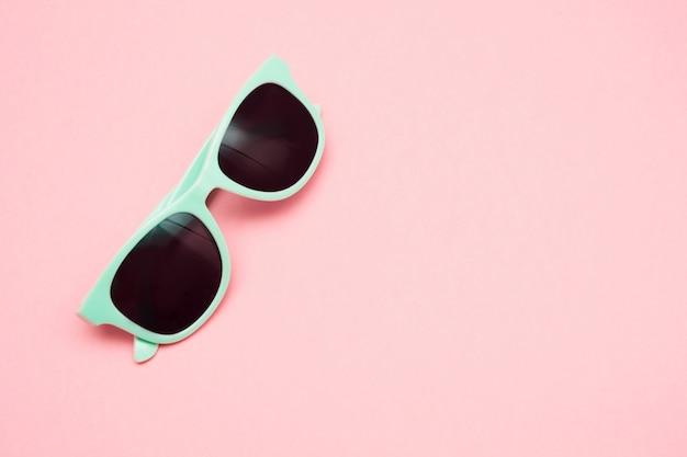Зеленые пастельные очки, изолированные на пробивной розовый, вид сверху. летняя концепция. Premium Фотографии