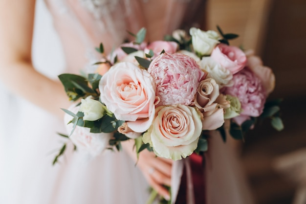 女性の手に牡丹、フリージア、その他の花を持つ花嫁のウェディングブーケ。軽くて薄紫色の春の色。部屋の朝 Premium写真