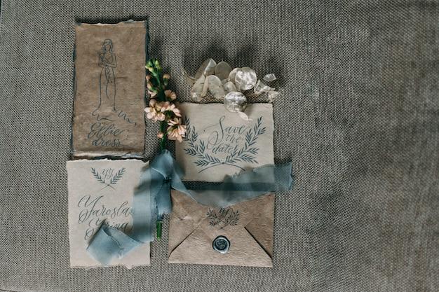 花とシフォンのボビンと美しい書道カードの結婚式の素朴でグラフィックアート。美しい結婚式の招待状。上面図。 Premium写真