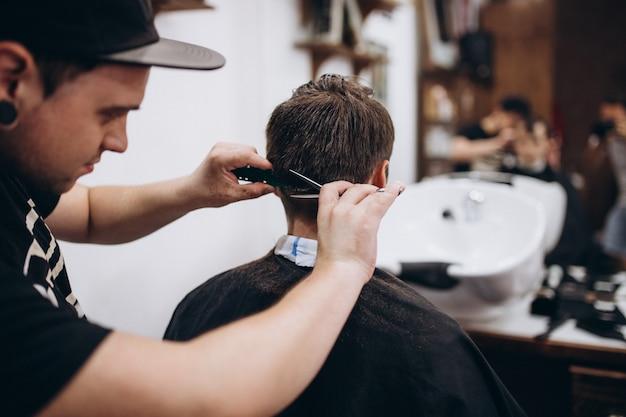 Мастер стрижет волосы и бороду мужчины в парикмахерской, парикмахер делает прическу для молодого человека Premium Фотографии