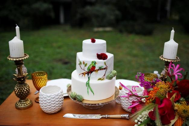Красивый свадебный трехъярусный торт украшен птицей, розовыми цветами и ветками с зелеными листьями в деревенском стиле. праздничный десерт. свадебная концепция Premium Фотографии