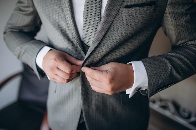 ジャケットをボタンモダンなフォーマルな服に身を包んだ若いハンサムなスタイリッシュな男。灰色のジャケット、紫のシャツの男の手のクローズアップ。結婚式のお祝いや卒業の準備ができている人。 Premium写真