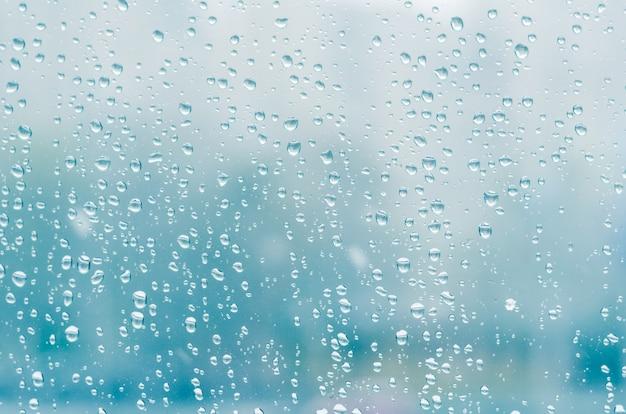 雨のしずくとウィンドウガラスの背景、青の調子に冷凍水 Premium写真