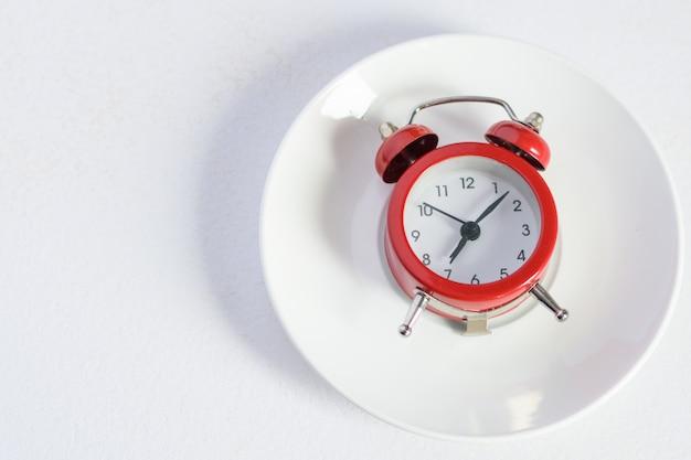 銀のスプーンで白いプレートに赤い目覚まし時計 Premium写真