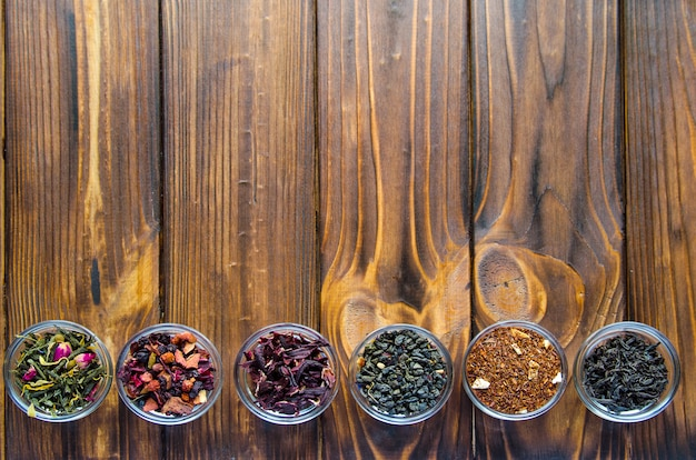 自然な木製の背景に透明な小さなボウルに各種お茶の選択 Premium写真