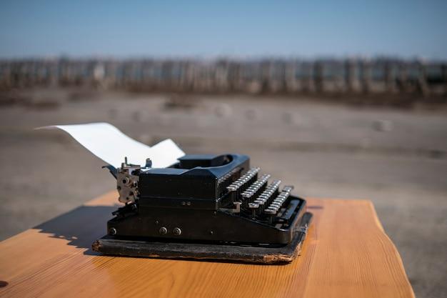 オープンエアのテーブルの上のタイプライター、背景の河口 Premium写真