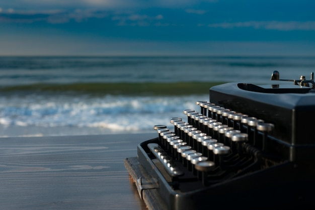 夜明けに海の背景にタイプライター。夏のビーチ Premium写真