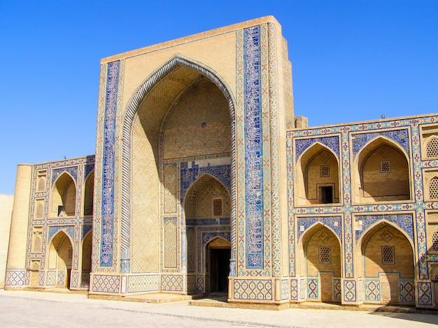 ウズベキスタンのブハラにある中央アジア最古の神学校であるウルグベクメドレッサの側面図。 Premium写真