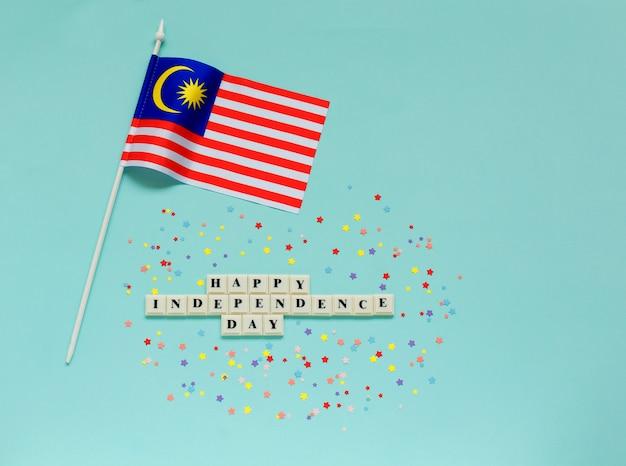 幸せな独立記念日の碑文とマレーシアの旗 Premium写真
