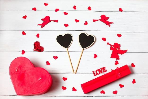 バレンタイン・デー。ギフト、キャンドル、紙吹雪、天使で作られたフレーム Premium写真
