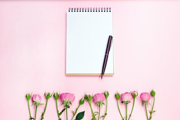 Цветок розы на пустой тетради Premium Фотографии