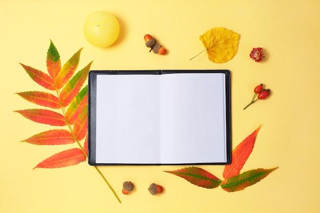 美しい乾燥した葉と黄色の背景上のノート。 Premium写真