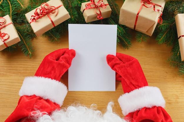 サンタクロースの手でクリスマスの手紙のクローズアップ Premium写真