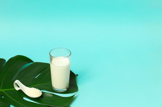 スプーンとヤシの葉の背景にミルクトップのガラスのコラーゲンパウダー Premium写真