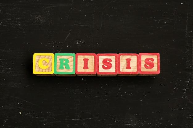 木製の文字から作られた単語の危機は黒いテーブルの上にあります。 Premium写真