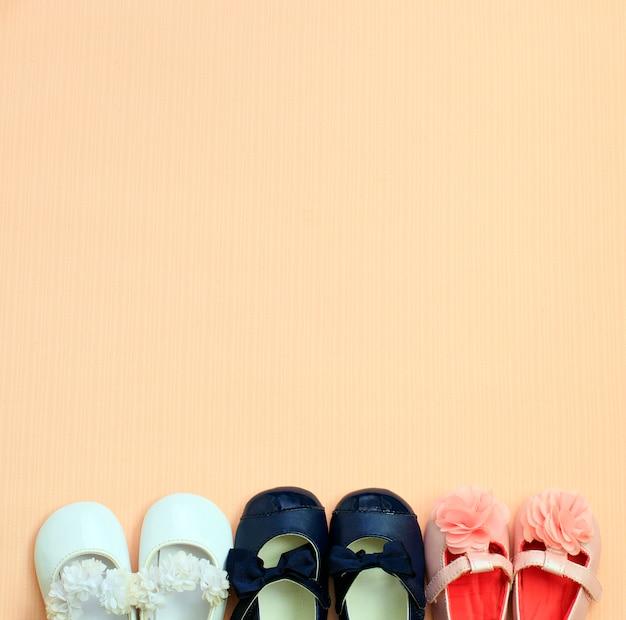 ピンクの背景、上面に配置された多くのかわいい赤ちゃんの靴 Premium写真
