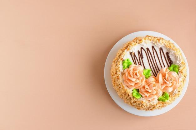 白い皿にクリーミーなバラのビスケットのクリームケーキ Premium写真