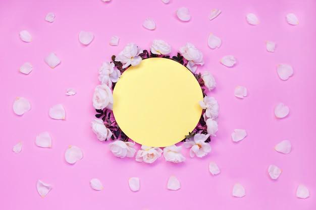 カラフルな明るい花の構図。白いバラの花と花びらで作られたフレーム Premium写真