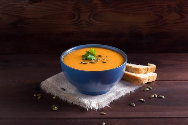 パセリ、オリーブオイル、カボチャの種を添えたボウルにカボチャのスープ Premium写真