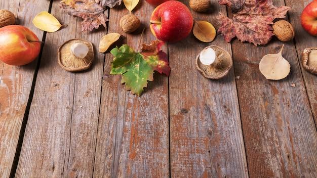 Картофельные грибы, яблоки, грецкие орехи и разноцветные листья на старых деревенских деревянных досках. осенний день благодарения фон, копия пространства Premium Фотографии
