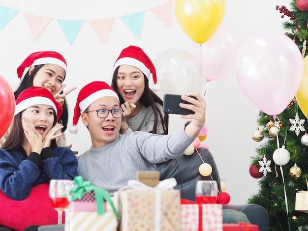 Группа азиатских людей весело провести время вместе в праздновании новогодней вечеринки у себя дома. Premium Фотографии
