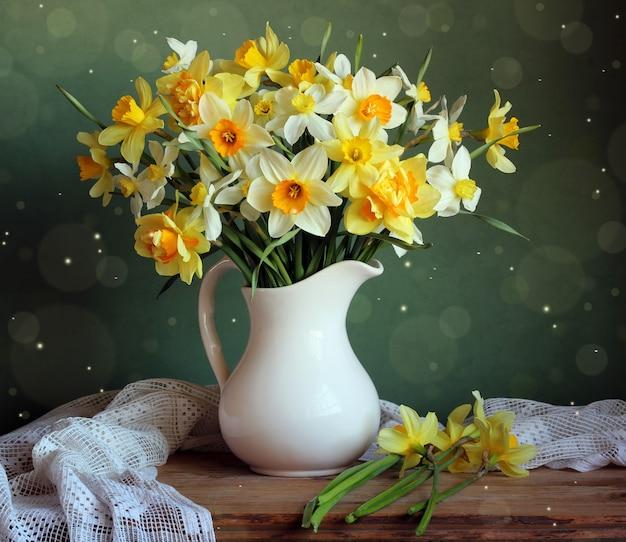 テーブルの上の白い投手の黄色い水仙。 Premium写真