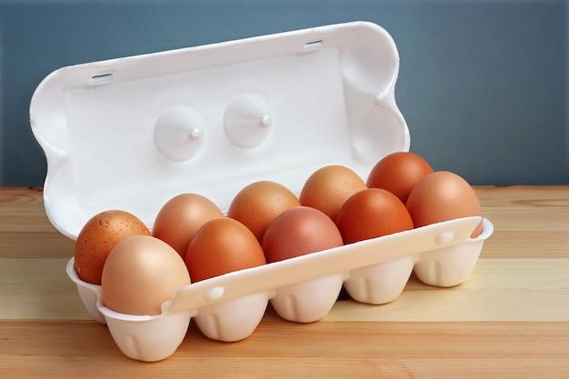 Десять куриные коричневые яйца в белом пенопластовом пакете на деревянный стол. Premium Фотографии