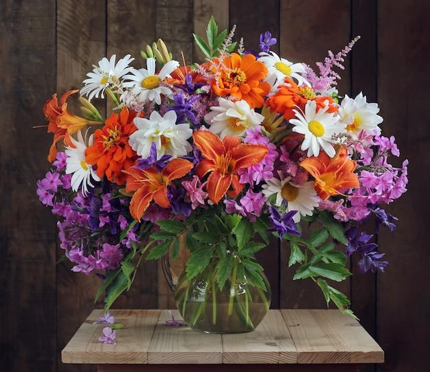花瓶に栽培された花の花束。ヒナギクとユリ、フロックスとダリア。 Premium写真