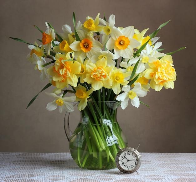 透明な水差しと白いテーブルクロスとテーブルの上のレトロな目覚まし時計で黄色の水仙の花束。静物。 Premium写真