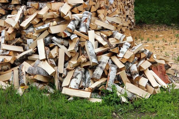 斧でみじん切り、草の上の丸太の山 Premium写真