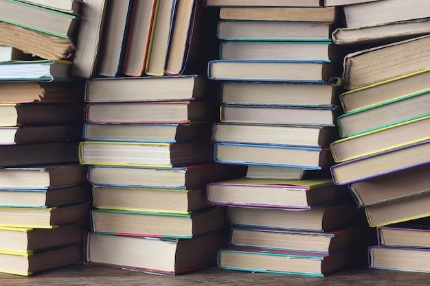 本からの背景。棚のクローズアップの本の山。としょうかん。学校に戻る。 Premium写真