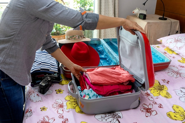 Женщина упаковывает багаж Premium Фотографии