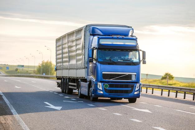 Прибывающий белый грузовик на дороге в деревенском пейзаже на закате Premium Фотографии