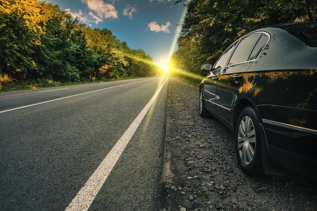 Черная машина на асфальтированной дороге Premium Фотографии