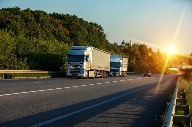 日没時の田園風景の道に白いトラックを到着 Premium写真