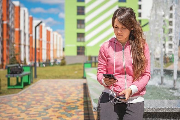 外部電源銀行からバッテリーを充電する黒いスマートフォンを保持している女性手 Premium写真