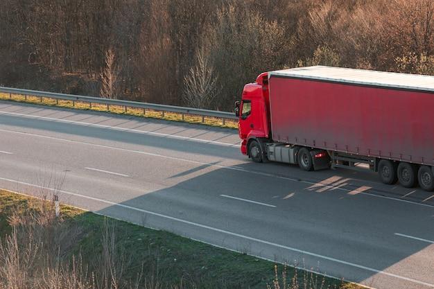 夕暮れ時の田園風景の中の道路に白いトラックを到着 Premium写真