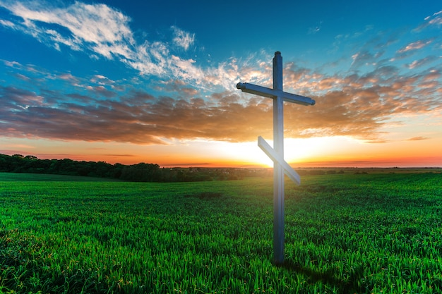 朝の緑の野原に木製の十字架。キリスト教の概念 Premium写真