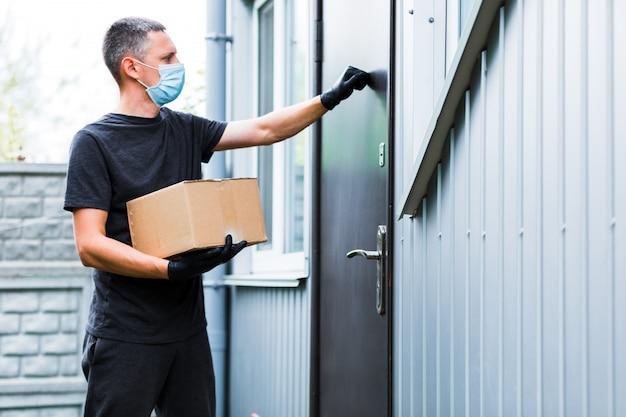 Доставка на дом, коробка для покупок, человек в перчатках и защитной маске, доставляющий посылки в дверь Premium Фотографии
