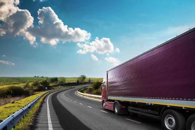 夕暮れ時の田園風景の道に白いトラックが到着 Premium写真