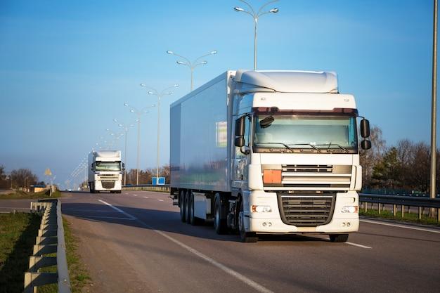 夕暮れ時の農村景観における道路上の白いトラックの到着 Premium写真