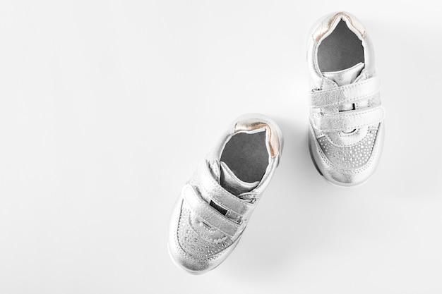 Квартира лежала. серебряная детская спортивная обувь на белом фоне Premium Фотографии