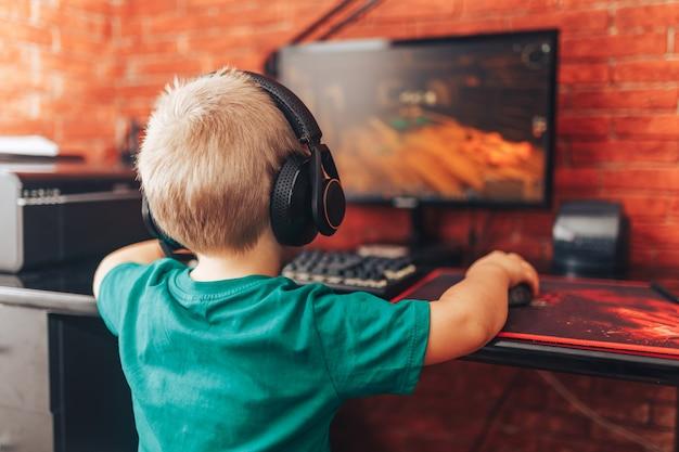 少年はマイク、コンピューターゲームとヘッドフォンでコンピューターでゲームをプレイ Premium写真