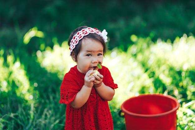 Девочка в красном платье ест грушу в летнем саду возле красного ведра Premium Фотографии