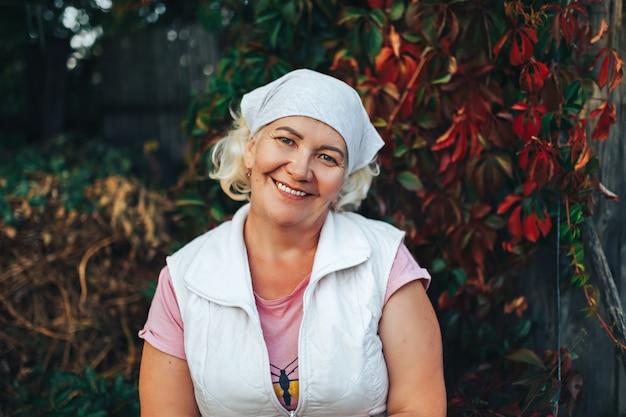 成熟した笑顔の女性庭師または彼女の頭にスカーフで庭に座っている女性 Premium写真