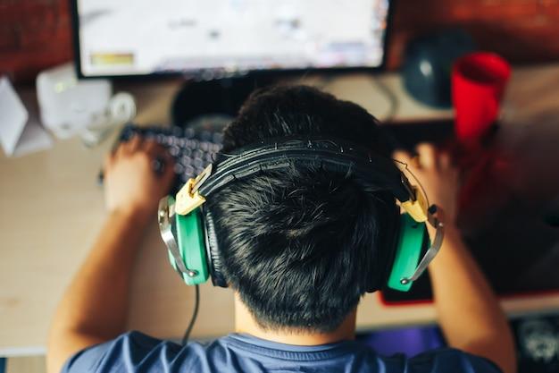 若い男がコンピューターでゲームをプレイ Premium写真
