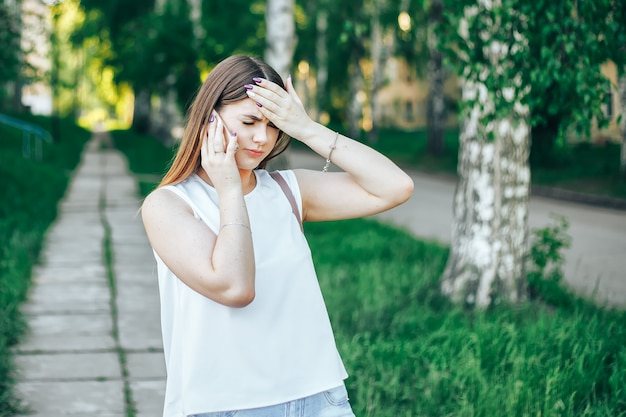 Молодая женщина с длинными волосами разговаривает по мобильному телефону и имеет головную боль Premium Фотографии