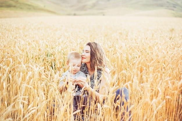 若くて美しい女性が小麦の牧草地で彼女の幼児の赤ちゃんと遊ぶこと。夏のコンセプトです。 Premium写真